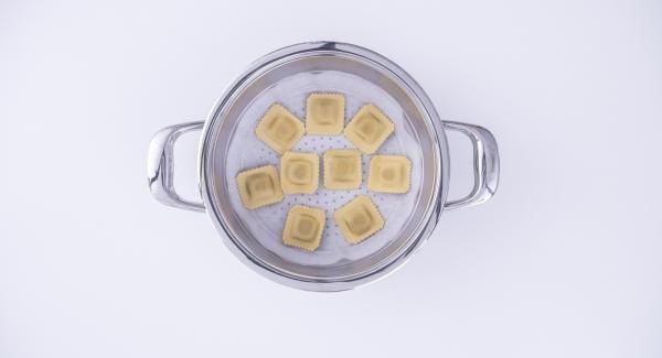 Adagiare all'interno dell'Unità di cottura l'acqua e la passata di pomodoro. Posizionare i ravioli su un disco di carta da forno e inserirlo nell'Inserto «2 in 1». Collocare l'Inserto «2 in 1» sopra l'Unità di cottura e coprire con EasyQuick.