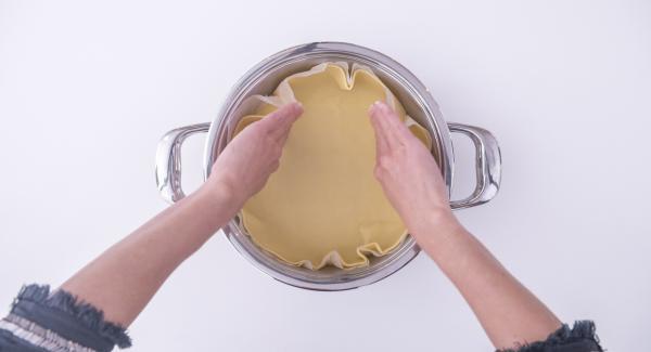 Lavorare la pasta frolla, stenderla e posizionarla all'interno dell'Unità di cottura 24 cm 2,5 l  su un disco di carta da forno leggermente più grande del fondo dell'Unità.