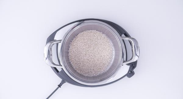 Adagiare il riso all'interno dell'Unità di cottura usando un bicchiere come unità di misura e procedere aggiungendo, per ogni bicchiere di riso, due bicchieri di brodo di pesce. Infine, aggiungere il misto di pesce.