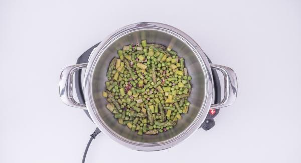 """Al suono di Audiotherm, rimuovere il coperchio, far rosolare lo speck e aggiungere i piselli e gli asparagi. Bagnare con il vino bianco. Impostare Navigenio in modalità """"A"""". Posizionare Audiotherm sulla finestra """"verdura"""" dopo aver impostato un tempo di cottura di 10 minuti."""