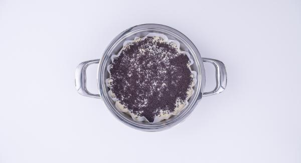 Ritagliare un disco di carta da forno di diametro che possa ricoprire il fondo e parte dei bordi interni dell'Unità di cottura. Adagiarvi l'impasto e guarnire con le granelle di cioccolato.