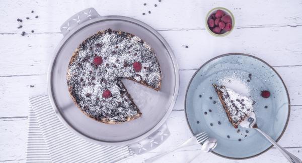 Al suono di Audiotherm, sollevare i lembi della carta da forno e posizionare la torta su un piatto da portata. Guarnire con lo zucchero a velo e servire.