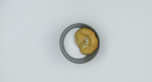Rotolare le frittelle nello zucchero e servirle ancora calde.