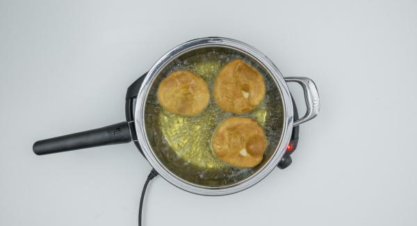 Togliere il coperchio, girare le frittelle e cuocere senza coperchio fino a doratura.