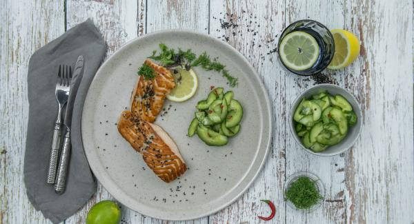Tritare finemente le foglie di aneto. Insaporire i filetti di salmone con sale e pepe, servirli con l'insalata di cetriolo e peperoncino e cospargerli con l'aneto e il sesamo.