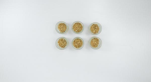 Ungere un poco i vasetti (da ca. 200 ml) con il burro, adagiarvi i biscotti tritati e premere leggermente.