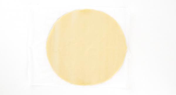 Stendere la pasta sfoglia e darle una forma circolare del diametro di ca. 28 cm. Tagliare un foglio di carta forno dello stesso diametro. Posare quindi la pasta sfoglia sulla carta forno.