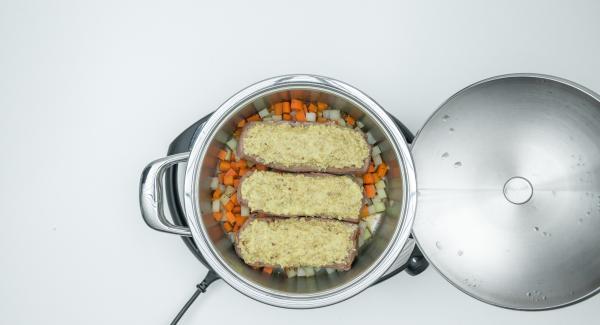 Spalmare il composto ottenuto sulla spalla di agnello. Condire le verdure con timo, miele, sale e pepe e adagiarvi sopra la carne.