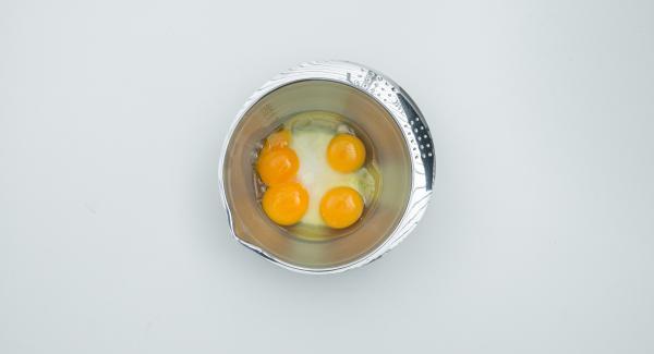 Mescolare lo zucchero rimanente con le uova e i tuorli. Unire il latte e la panna e versare il composto sul caramello.