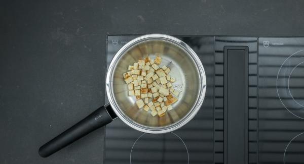 Ridurre a pezzetti le fette di pane e tostare nella Sauteuse a calore basso fino a doratura.