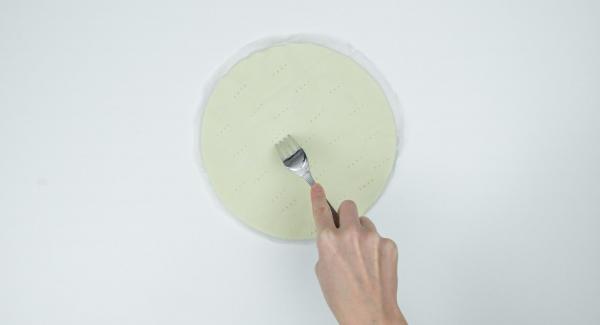 Stendre la pasta sfoglia di circa 24 cm Ø e bucherellarla con una forchetta. Tagliare la carta da forno leggermente più grande della base della pasta in modo che la torta possa essere estratta dall'Unità con più facilità al termine della cottura.