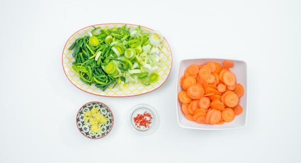 Mondare il porro e tagliarlo ad anelli. Pelare le carote e affettarle molto sottilmente. Pelare lo zenzero e grattugiarlo finemente, privare dei semi il peperoncino e tritarlo finemente.