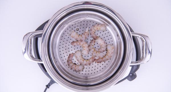 Versare dell'acqua (120 ml) nell'Unità di cottura posizionata su Navigenio, mettere i gamberoni nella Softiera e posizionarla all'interno dell'Unità.