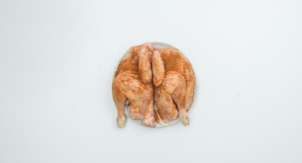 Tagliare a metà il pollo, insaporire con la spezia AMC Intenso e lasciar marinare.