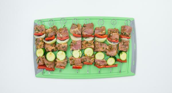 Lavare a pulire i peperoni e le zucchine. Tagliarle a pezzetti di dimensioni idonee per gli spiedini. Disporre la carne e le verdure in modo alternato su 8 spiedini.