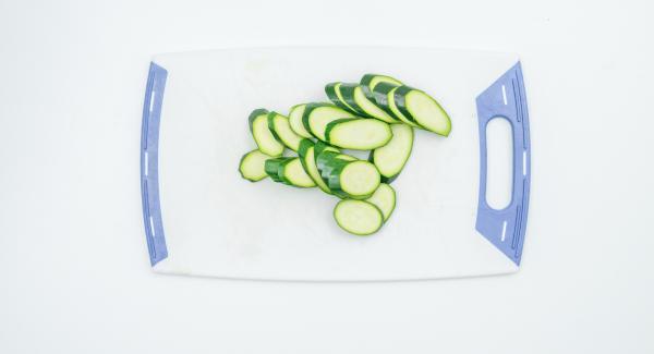 Tamponare il pesce con carta da cucina. Mondare e affettare le zucchine, il pomodoro e il limone.