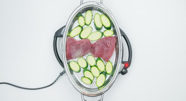 Al suono di Audiotherm, abbassare Navigenio a livello 4 e adagiare i filetti all'interno dell'Unità insieme alle zucchine, prestando attenzione a non sovrapporre i due alimenti