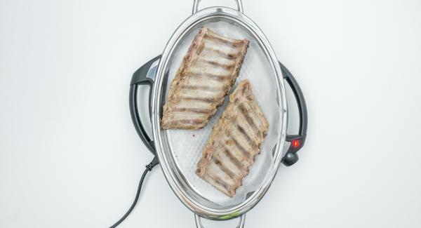 Al suono di Audiotherm, abbassare Navigenio a livello 4, posizionare la carta da forno nell'Unità Ovale Grill, disporvi le costine con la parte superiore rivolta verso il basso.