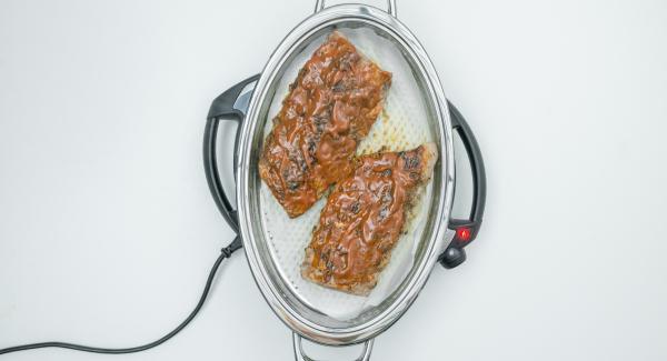 """Con l'ausilio di Audiotherm arrostire le costine fino a raggiungere il """"punto di girata"""" a 90° C. Girare le costine e spennellare la parte superiore con la salsa."""
