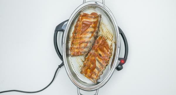 Chiudere il coperchio e attendere nuovamente il raggiungimento dei 90°C. Girare quindi le costine, spennellare con la salsa anche la parte inferiore e richiudere il coperchio.