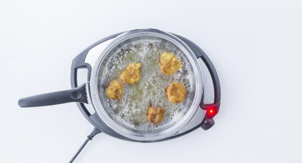 """Al suono di Audiotherm, al raggiungimento del """"punto di girata"""" a 90° C, girare le frittelle e coprire nuovamente con il coperchio. Ruotare Audiotherm fino a visualizzare il simbolo """"carne"""" e lasciar dorare le frittelle fino al suono. Togliere le frittelle dalla Padella."""