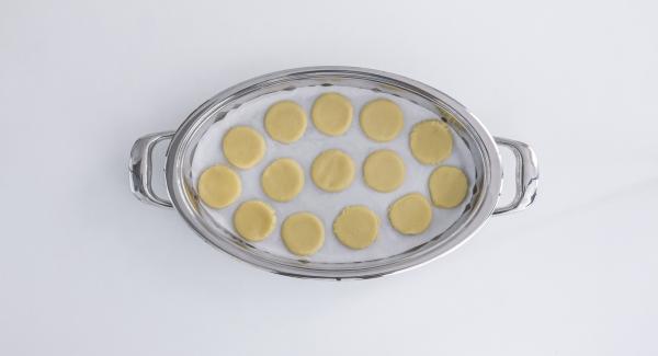 Disporre della carta da forno nell'Unità Ovale fredda e distribuirvi sopra i biscotti.