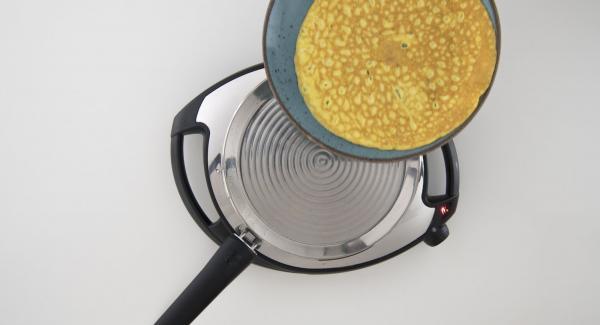 Con l'aiuto di un piatto, girare la frittata e far cuocere dall'altro lato. Tenere da parte la frittata.