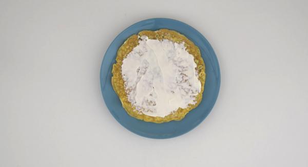 Lavare e tagliare a fette il pomodoro. Spalmare il formaggio cremoso sulla frittata, mettere sopra le fette di prosciutto, l'insalata e infine i pomodori.