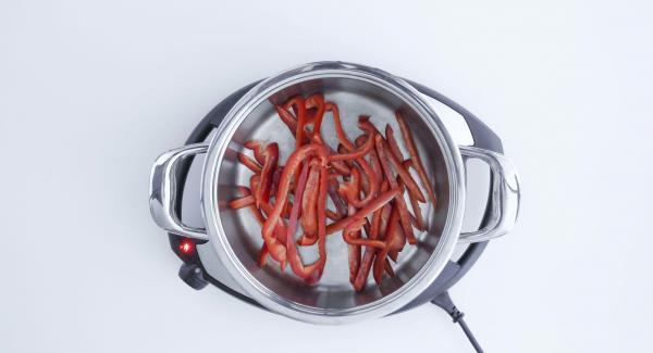 Tagliare i peperoni a striscioline e metterle nell'Unità di cottura. Distribuirvi sopra i dadini di pomodoro, cipolla e aglio e irrorare il tutto con 2 cucchiaini di olio di oliva.