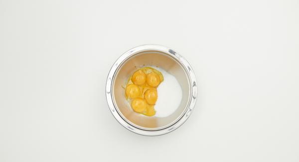 Mescolare i tuorli con lo zucchero. Aprire i bastoncini di vaniglia, estrarre i semi con un coltello piccolo e aggiungerli all'impasto. Aggiungere il latte, la panna e la zucca passata e mescolare fino ad ottenere un impasto omogeneo.