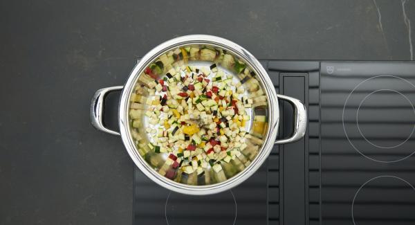Al suono di Audiotherm, abbassare il calore e lasciar rosolare il trito di cipolla e aglio. Aggiungere quindi i cubetti di calamari, rosolare brevemente e toglierli dalla Padella. Rosolare le verdure miste a dadini allo stesso modo, insaporire con sale e pepe, infine mescolare e unire i pomodori e le erbe aromatiche.