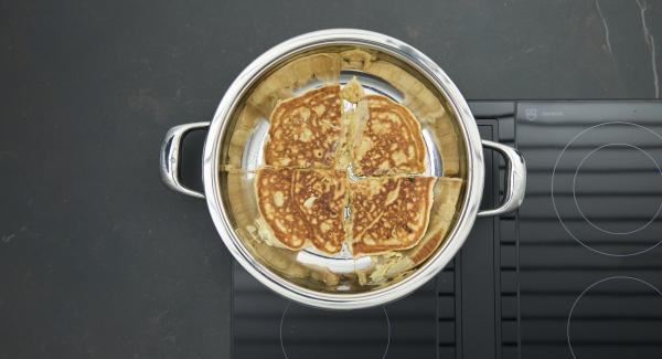 Spegnere il calore. Tagliare in quattro la frittata e girarla (se la pastella non è cotta a sufficienza, coprire con il coperchio e attendere un poco).