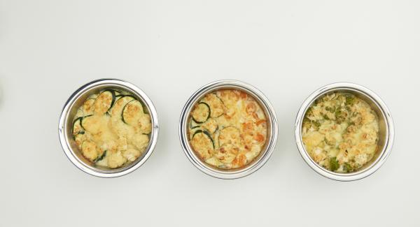 Grattugiare o tagliare a fette o a dadini il formaggio. Togliere il coperchio, distribuirvi sopra il formaggio e far gratinare senza coperchio per ulteriori 10 minuti.