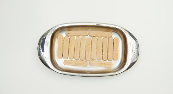 Disporre uno strato di savoiardi all'interno della Lasagnera, cospargere metà della composta di arance e lasciar riposare per qualche minuto.