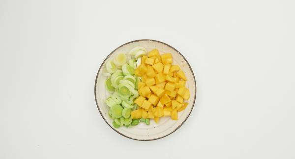 Mondare il porro e tagliarlo ad anelli. Sbucciare il mango, separare la polpa dal nocciolo e tagliarla a dadini.