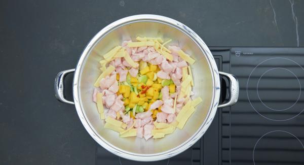 Mettere nel Wok il porro bagnato e due terzi dei dadini di mango. Distribuirvi sopra il peperoncino tritato, i germogli di bambù e i pezzetti di pesce.