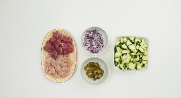 Tagliare il pollo e la bistecca di manzo a dadini di 1-2 cm. Pelare la cipolla, pulire le zucchine e tagliare entrambe a dadini. Fare altrettanto con i cetriolini.