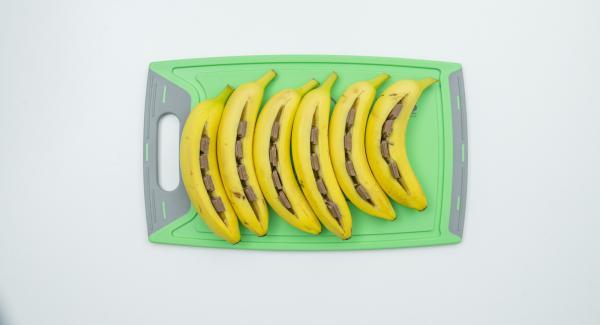 Lavare accuratamente le banane con la buccia e asciugarle. Con un coltello inciderle per il lungo (non tagliarle completamente), aprire leggermente l'apertura con le dita e riempirla con i pezzetti di cioccolato (il cioccolato non deve sporgere al di fuori dell'apertura, altrimenti fuoriesce durante la preparazione).