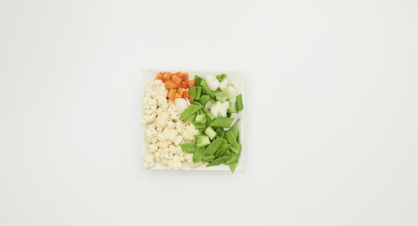 Pulire il cavolfiore, i fagioli e i cipollotti e pelare le carote. Tagliare le verdure a bocconcini