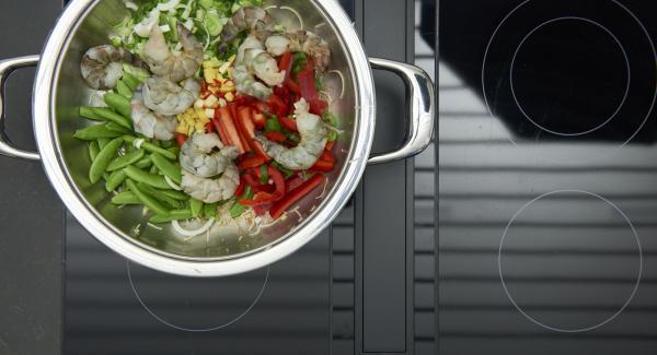 Rosolare la pasta a calore vivace e toglierla. Rosolare brevemente anche i cipollotti, il pomodoro, il peperoncino, l'aglio e lo zenzero. Aggiungere i gamberetti e continuare la cottura.