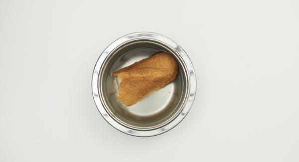 Ammollare il pane in acqua calda, strizzarlo e spezzettarlo