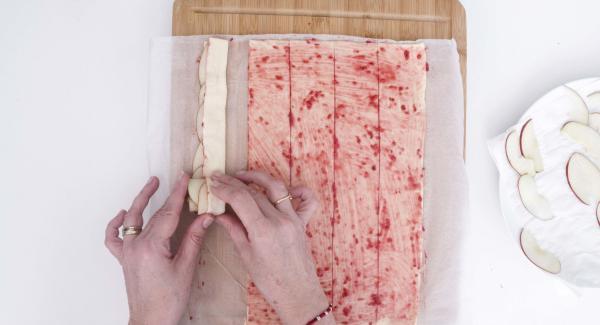 Piegare a metà la pasta sfoglia, lasciando i pezzetti di mela al centro e arrotolare.