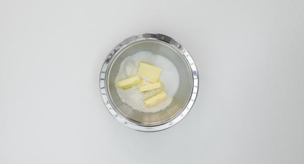 Versare in una scodella la farina, le scaglie di cocco, lo zucchero, il sale e il burro e lavorare finché si formano delle briciole. Mettere in frigo per 30 minuti circa.