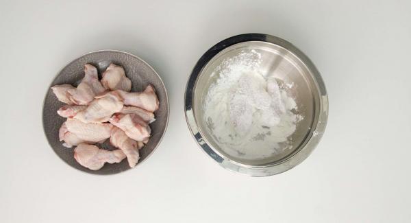 Passare le ali di pollo nella farina, togliendo poi l'eccesso.
