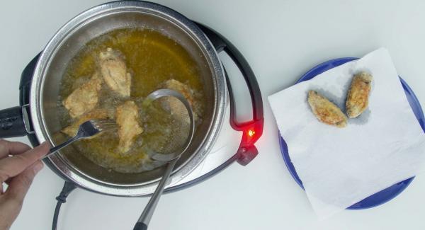 Asciugare con carta da cucina l'umidità dal coperchio e salare. Aggiungere il resto delle ali di pollo e friggerle mantenendo Navigenio a livello 4.