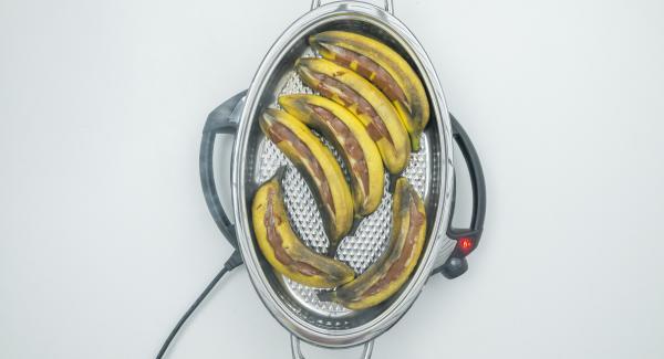 """Con l'aiuto di Audiotherm, cuocere fino a raggiungere il """"punto di girata"""" a 90 °C. Togliere il coperchio, estrarre le banane, sbucciarle e tagliarle ai lati."""