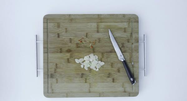 Tagliare l'aglio a fettine e tritare il peperoncino secco