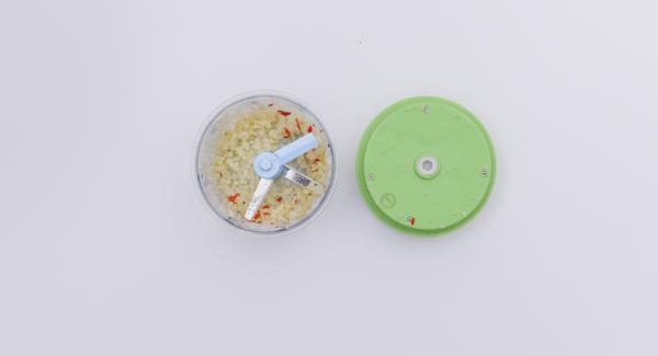 Pelare le cipolle e l'aglio, privare dei semi i peperoncini e tritare il tutto finemente nel Tritamix.