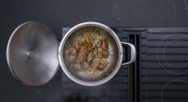 Al suono di Audiotherm, abbassare il calore e rosolare lo spezzatino su tutti i lati. Aggiungere il trito di cipolla e continuare a rosolare per breve tempo.