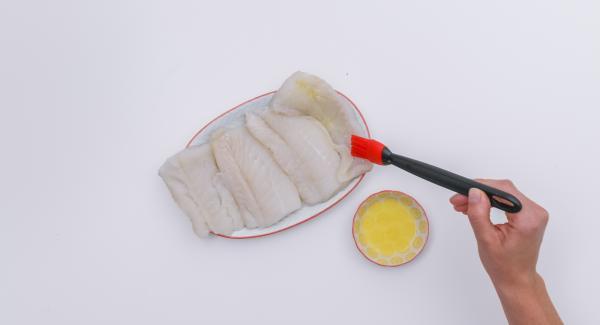 Tamponare i filetti di pesce e adagiarli su un foglio di carta da forno. Spennellare un lato con un po' di burro, girarli e condire con sale e pepe.